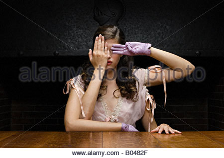 A woman with four arms covering her eyes - Stock Photo
