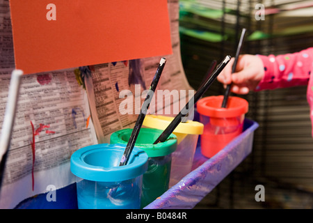 A girl putting a paintbrush in a paint pot - Stock Photo