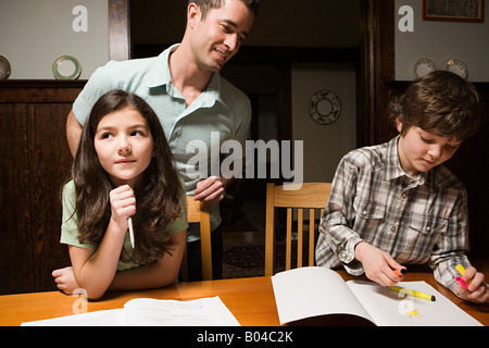 A father supervising his childrens homework - Stock Photo