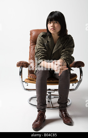 Japanese woman sitting on a leather armchair - Stock Photo