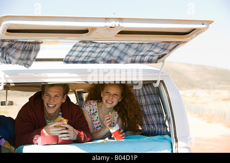 A couple eating fast food in a camper van - Stock Photo