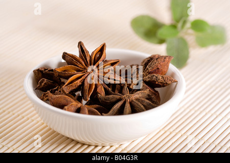 dried star anise in small white china bowl on straw mat, garnisched with leaves - Stock Photo