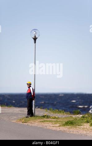 A man standing at seashore with yellow helmet on at Nallikari Oulu , Finland - Stock Photo