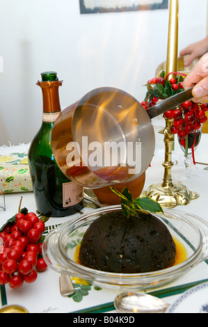 Pouring lit brandy over the christmas pudding - Stock Photo