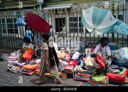 Women sitting in street selling bags and umbrellas,Port Louis market, Mauritius - Stock Photo