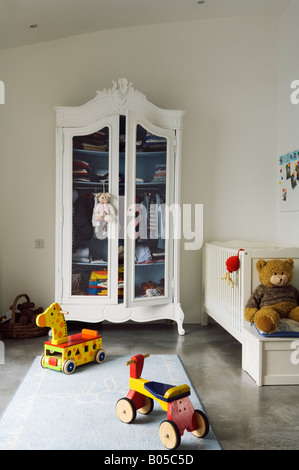 Child's room in converted 1950s factory with wardrobe and toys - Stock Photo