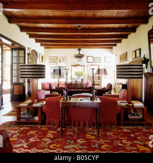 sitting room with patterned rug and beamed ceiling in a South African Dutch Cape homestead - Stock Photo