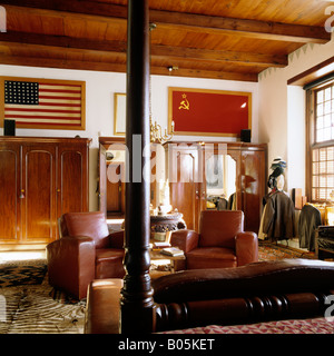 Bedroom with beamed ceiling and leather chairs in South African Dutch homestead - Stock Photo