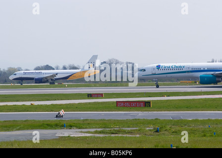 Monarch Airbus A320 Arriving and First Choice Boeing 757 About to Depart Manchester Airport England United Kingdom - Stock Photo