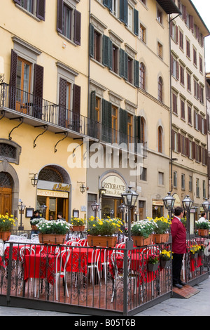 Outdoor cafe with red tablecloths ready for customers in Piazza della Signoria in Florence Italy - Stock Photo