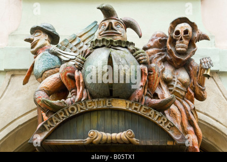 Horizontal close up of the wooden figures above the doorway of the Marionette Theatre in Prague. - Stock Photo