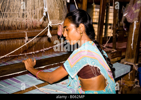 Woman working at a loom in a weaving factory, Madurai, Tamil Nadu, India - Stock Photo
