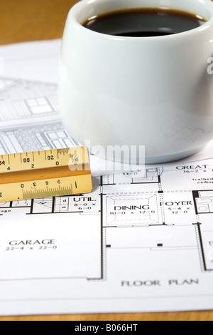 ... Home design drawings and a coffee on an architects desk - Stock Photo
