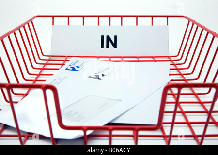 red wire mesh office post in tray for incoming mail with two bills - Stock Photo