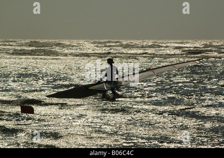 surfer in backlighting on rough seas - Stock Photo