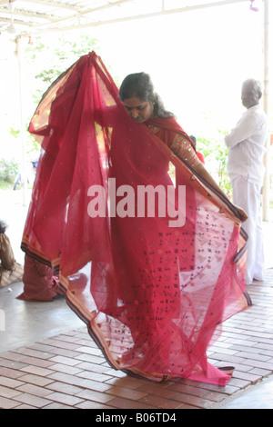 Hindu Woman folds a sari at Temple of fine arts in Brickfields Kuala Lumpur Malaysia - Stock Photo