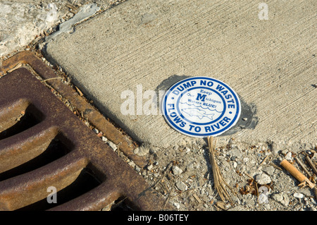 Storm drain with sign saying dump no waste flows to river in Ann Arbor Michigan USA - Stock Photo