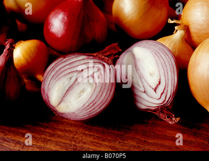 CUT RED ONION SURROUNDED BY WHOLE RED AND WHITE ONIONS ON A WOODEN SURFACE - Stock Photo