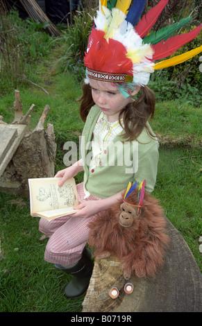 Nostalgic scene of little girl reading in allotments - Stock Photo