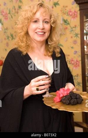 Closeup of Caucasian Woman (40-50) Holding Black Diamond French Truffles and Glass of Wine USA - Stock Photo