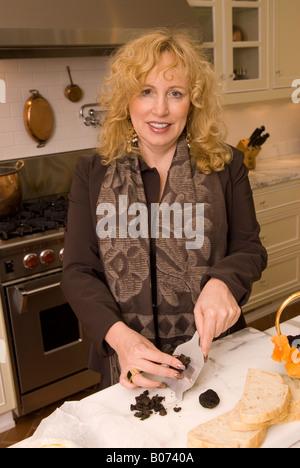Closeup of Caucasian Woman (40-50) Preparing Black Diamond Truffles Sandwich with Sourdough Bread and Cheese USA - Stock Photo