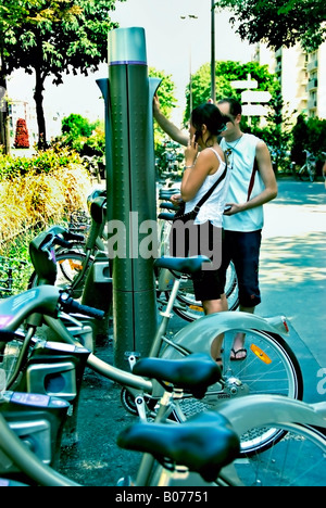 Paris France, Young People Renting Bicycle Sharing Velib  on Street, Public Access Bike Scheme docking station - Stock Photo