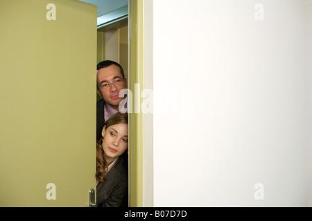 Woman peeking out door Stock Photo: 21802836