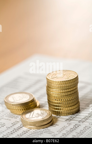 Stacked coins on a list - Stock Photo