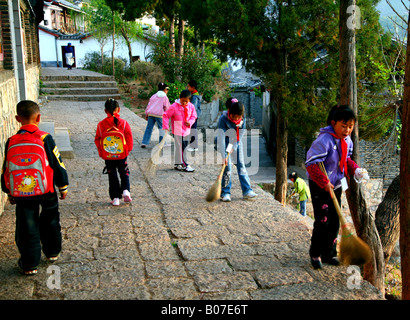 Schoolchildren sweeping a lane in Lijiang Old Town, China. - Stock Photo