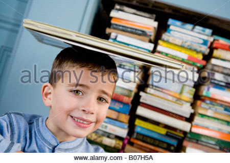 little boy with book balanced on his head - Stock Photo