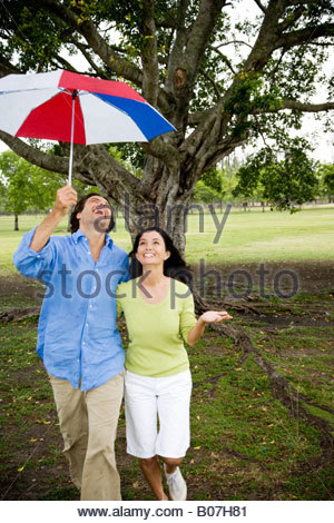 couple with umbrella walking in the park - Stock Photo
