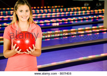 Teenage girl in bowling alley holding a red bowling ball - Stock Photo