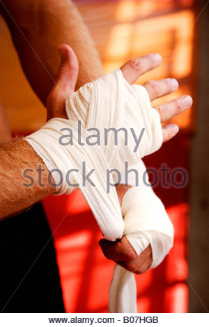 Boxer binding up hands with padding bandages - Stock Photo