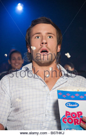Shocked man watching a film at the cinema throwing popcorn in the air in shock - Stock Photo