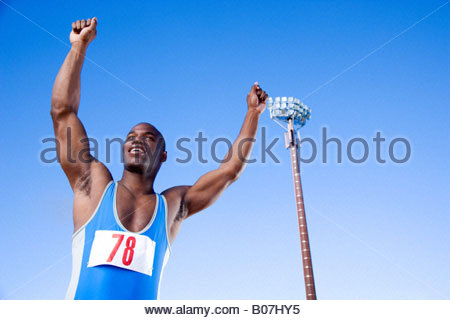 Portrait of an athlete with arms raised - Stock Photo