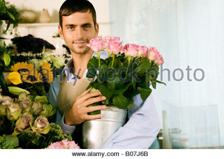 Male florist in his shop, holding a pot of pink roses - Stock Photo