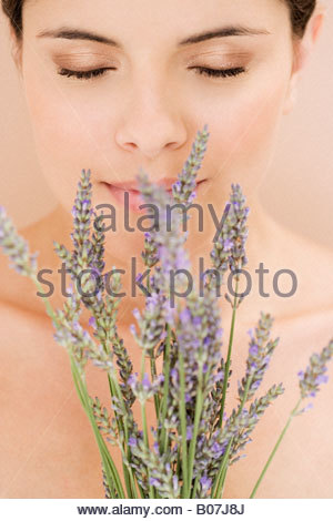 Young woman smelling lavender flowers - Stock Photo