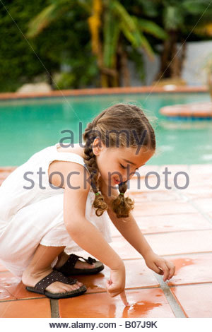 little Hispanic girl playing by the pool - Stock Photo