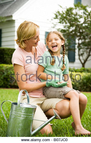 girl sitting on mother's lap laughing in the garden - Stock Photo