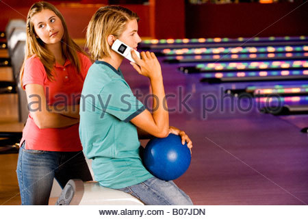 Teenage boy and girl in a bowling alley, boy talking on a mobile phone - Stock Photo