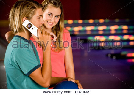Teenage boy and girl in a bowling alley, boy talking on mobile phone - Stock Photo