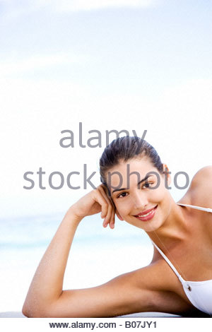 Portrait of young woman lying on the beach - Stock Photo