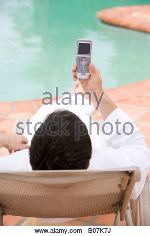Man sitting by a swimming pool, using a mobile phone - Stock Photo