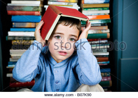 little boy with book on his head - Stock Photo