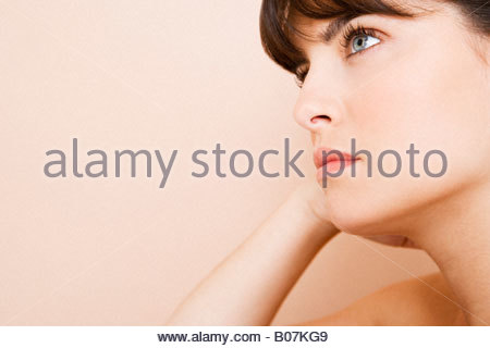 Young woman looking pensive, thinking - Stock Photo
