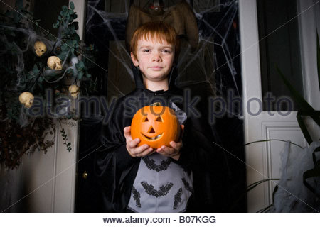 Boy in a skeleton costume at Halloween, holding a pumpkin with a carved face - Stock Photo