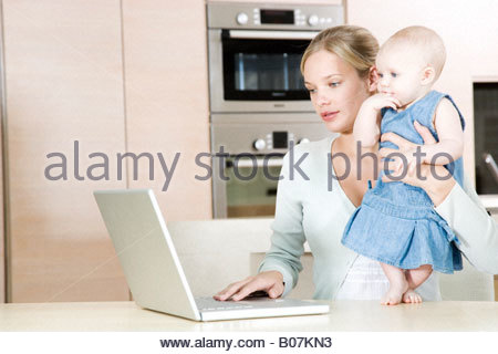 Mother using a laptop in the  kitchen at home, holding baby daughter - Stock Photo