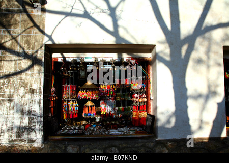 Souvenir stall and tree shadows in an alley in Lijiang's Old Town. - Stock Photo