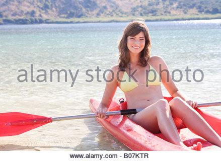 young woman in a sea kayak paddling sea kayaking mountains behind