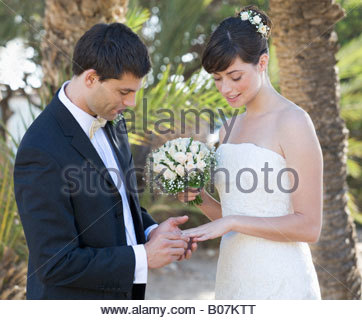A groom placing the ring on his bride's finger at their marriage - Stock Photo